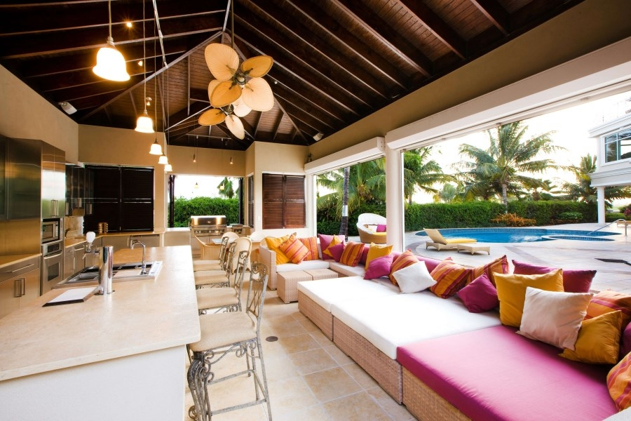 outdoor kitchen with overhang and ceiling fans in tropical setting