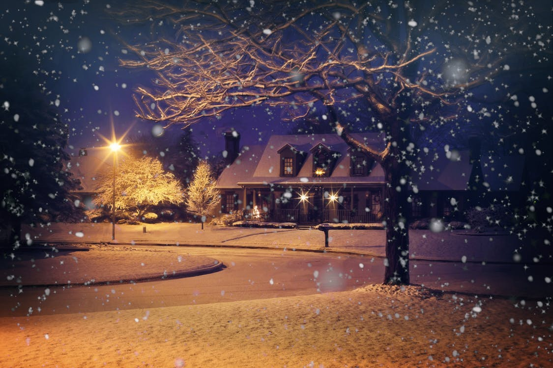 photo of a home at night during snowfall in winter