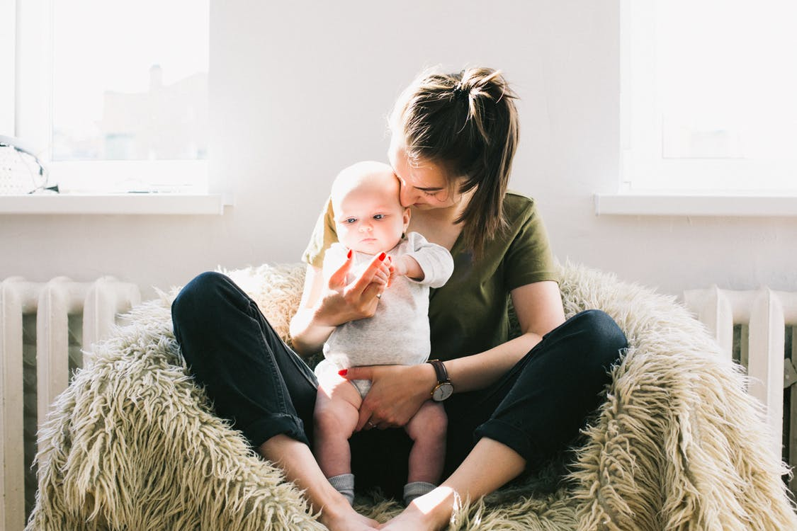mom holding baby in nursery
