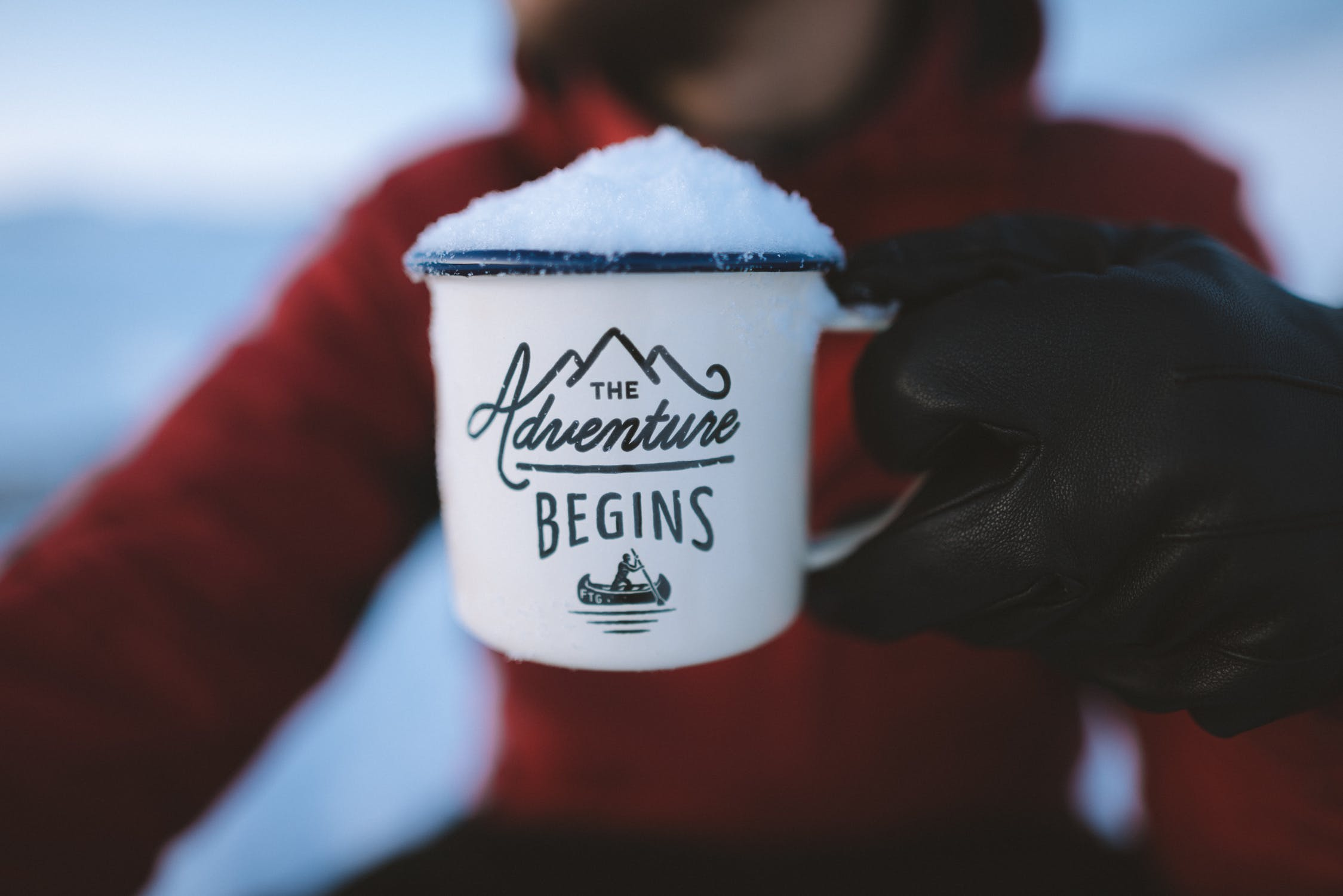 person holding mug filled with snow
