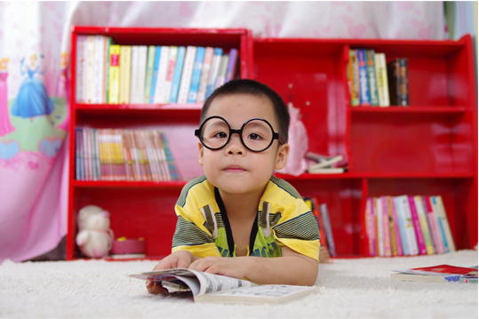kid sitting in front of books