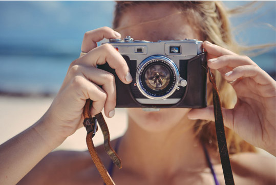 girl at beach holding camera to her face