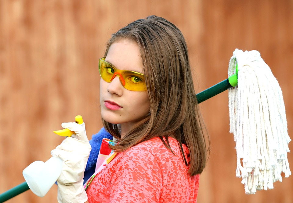 girl holding cleaning products clean