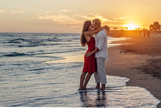 couple kissing on beach at sunset