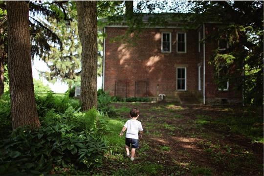 little boy walking towards a home
