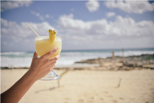 hand holding a pina colada on the beach