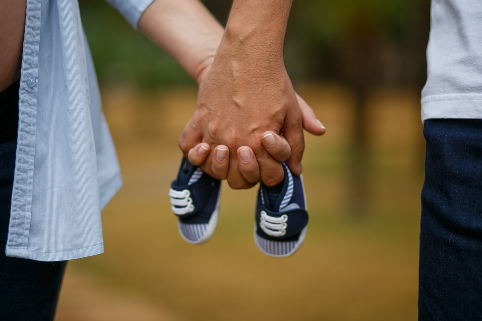 man and woman holding hands with baby shoes
