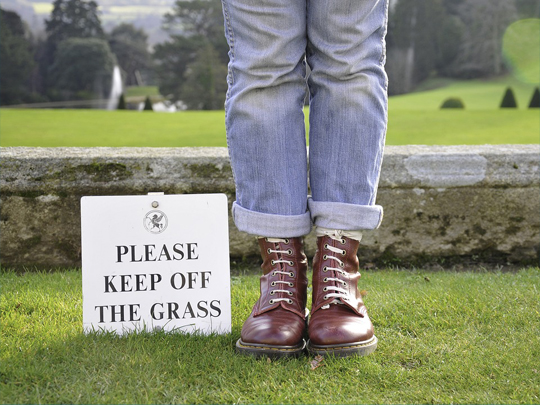booted legs standing near keep off the grass sign