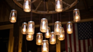 Decorative mason jars with lights hanging from a ceiling