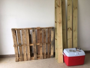 Plastic cooler with wooden planks next to it