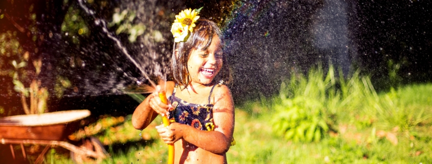 Little girl playing with a sprinkler