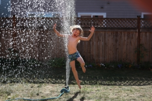 Little boy jumping in a sprinkler