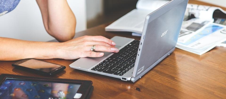 female hands on laptop keys